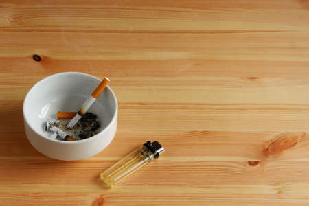 Many cigarette with white ashtray and lighter on wooden table Stockfoto