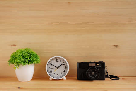 Table clocks and flower vases and film cameras on wooden desks. with copy space for text.