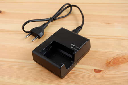 Camera battery charger with power cable on wooden desk.