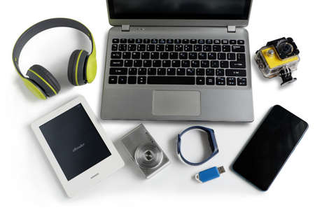 Laptop computer with smartphone and camera and ebook reader and other obsolete electronic gadgets on white background,Top view, Reuse and Recycle concept