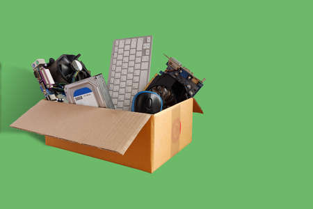 Hard disks and motherboards and old computer hardware accessories, Electronic waste in paper boxes isolated on green background, Reuse and Recycle concept. 스톡 콘텐츠