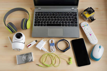 Laptop computer with smartphone and camera and other electronic gadgets on wooden background.Top view. 스톡 콘텐츠