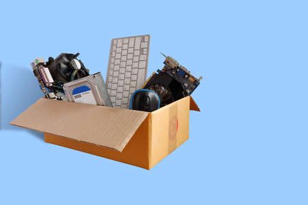 Hard disks and motherboards and old computer hardware accessories, Electronic waste in paper boxes isolated on blue background, Reuse and Recycle concept.