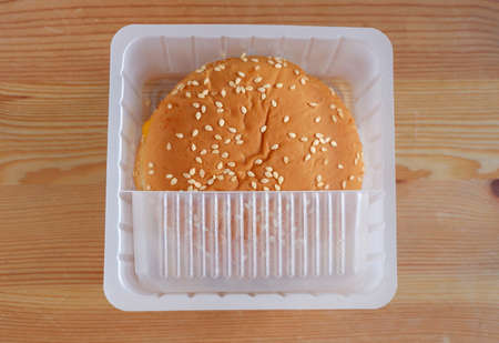 Top view of hamburger buns in plastic box on wooden background, Disposable plastic containers are an environmental problem. 스톡 콘텐츠