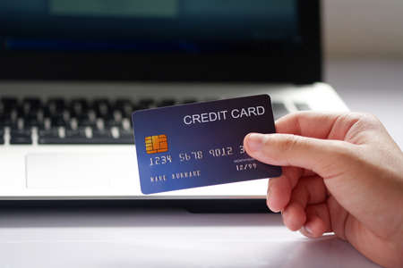 Female hand holding credit card and laptop computer on white desk. Concept of Online shopping and payment.