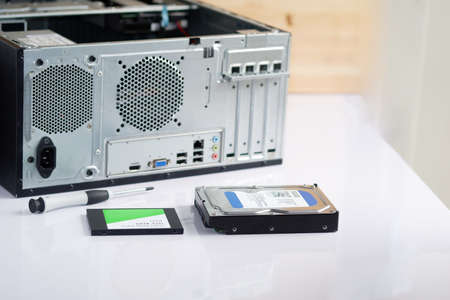 Hard drive and ssd with a screwdriver upgrade and repair desktop computer internal parts, selective focus