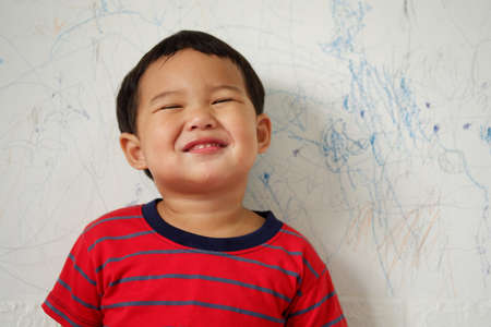 Cute smiling Asian boy wearing a bright red striped T-shirt standing on white background. with text copy space, Selective focus