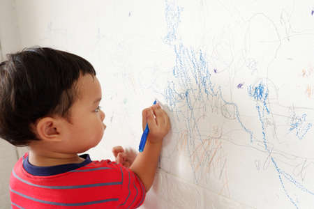 Cute asian boy in bright red striped t-shirt stands scribbling on white wall. with text copy space, Selective focus