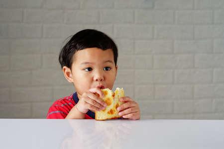 Cute little asian boy eating bread enjoying breakfast or snack on white table 스톡 콘텐츠