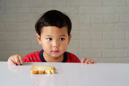 Cute little asian boy has an bored expression and is eating bread on a white dining table