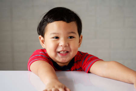 Cute little asian boy smiles in a good mood and sees rotten teeth on white table. 스톡 콘텐츠