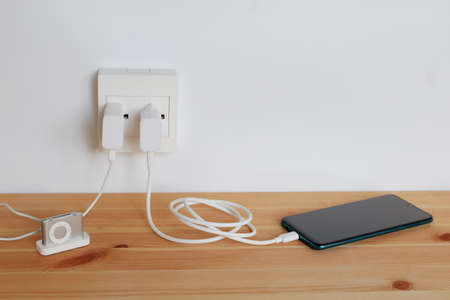 Plug in power outlet Adapter cord charger of smart phone and mp3 players, gadgets, on wooden floor