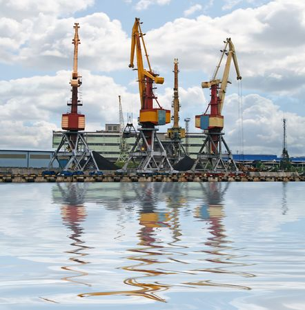Container cranes for loading and unloading ships. Reflection over water. photo