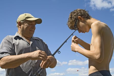 Fishers holding a fish caught on a fishing line photo