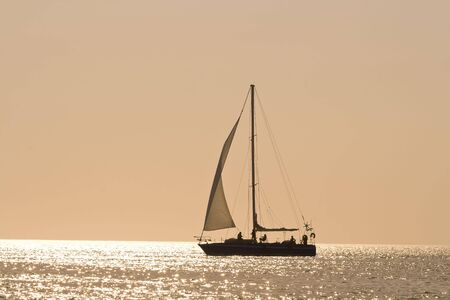 People on a sail boat at the sunset photo