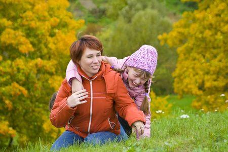 clamber: La mamma con una figlia arrampicarsi in salita. Su uno sfondo di cespugli con foglie gialle.