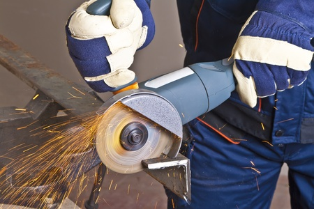 industrial tools: A man working with grinder, close up on tool, hands and sparks, real situation picture