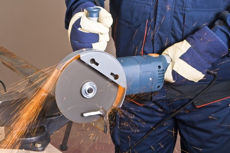 grinder machine: A man working with grinder, close up on tool, hands and sparks, real situation picture