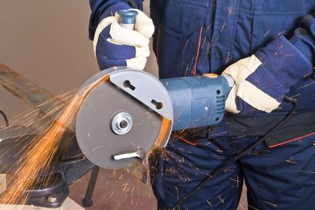 meuleuse: Un homme travaillant avec moulin, gros plan sur l'outil, des mains et des �tincelles, une image vraie situation