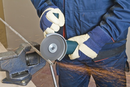 electric saw: A man working with grinder, close up on tool, hands and sparks, real situation picture