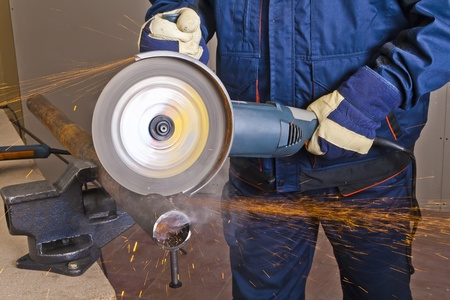 A man working with grinder, close up on tool, hands and sparks, real situation picture photo