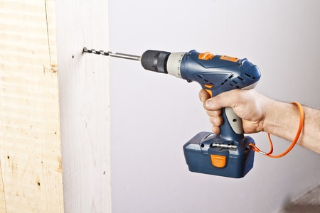 A man drilling a hole in wooden block photo