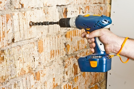 A man drilling a hole in the brick wall. photo