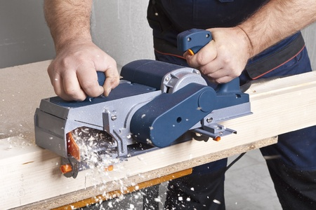 filings: Close-up of a construction workers hand and power tool while planing a piece of wood trim for a project. Stock Photo