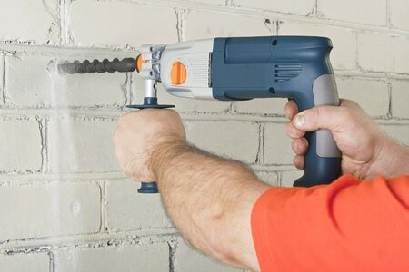 perforator: Builder hold perforator and drilling brick wall