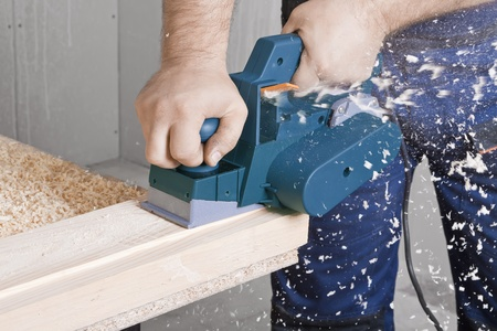Close-up of a construction workers hand and power tool while planing a piece of wood trim for a project. photo