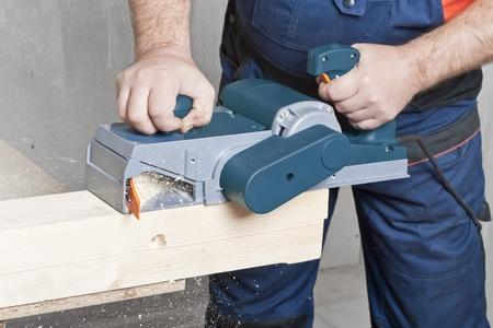 planos electricos: Primer plano de la mano de un trabajador de la construcci�n y herramienta de energ�a mientras la planeaci�n de un pedazo de madera recortar para un proyecto.