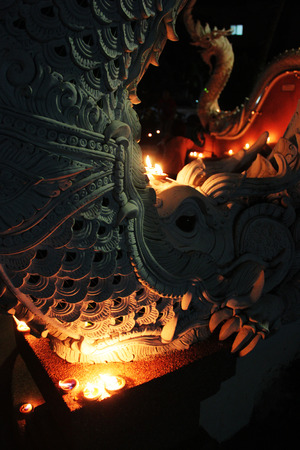 festivities: A candle illuminates the scales of a naga sculpture at a temple in Chiang Mai, Thailand during Loy Krathong festivities.