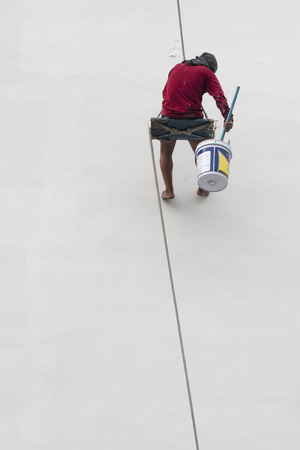 constant: BANGKOK, THAILAND - MAY 18: An unidentified man with no shoes paints a wall on May 18, 2012 in Bangkok, Thailand. Safety issues is a constant problem for low class and migrant laborers in the country.
