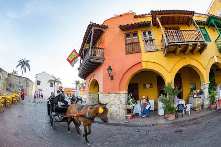 CARTAGENA, COLOMBIA - MAY 22: Unidentified tourists ride on a traditional horse drawn cart in front of the Donde Fidel restaurant in Cartagena, Colombia on May 22, 2016. Editorial