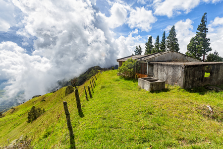 A fence disappears into the distance with clouds in the background and an abandonded cement house on a ridgetop between Quindio and Tolima, Colombia.