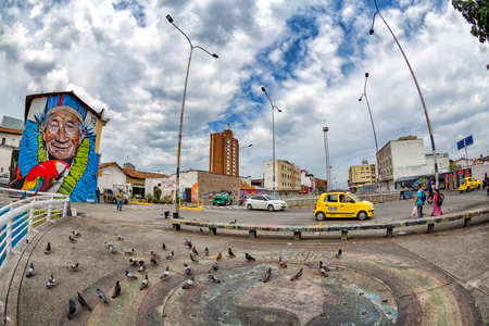 CALI, COLOMBIA - JUNE 10: Unidentified people walk past a small plaza with pigeons in Cali, Colombia on June 10, 2016. Editorial