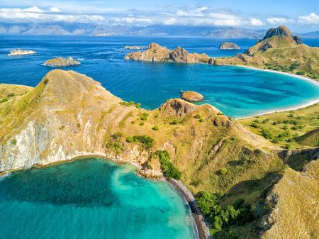 코모도와 인도네시아의 Labuan Bajo 근처 Rinca 제도 사이의 풀 라우 Padar 섬에 두 아쿠아 마린 베이의 공중보기. 스톡 콘텐츠