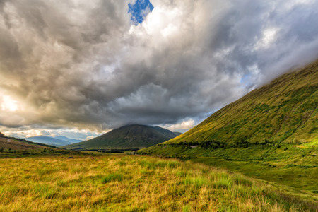 Verdant grass in a valley with Beinn Dorain and Beinn Odhar mountains in the background. Stock Photo