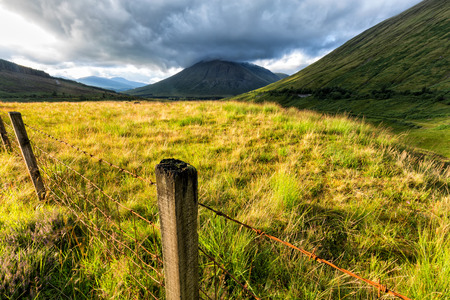Fencepost with Beinn Dorain and Beinn Odhar in the distance. Stock Photo