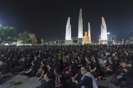 BANGKOK, THAILAND - OCTOBER 26: Unidentified mourners in black sit and watch the royal activities for the cremation of Rama 9, the former king next to Democracy Monument in Bangkok, Thailand on October 26, 2017. Editorial