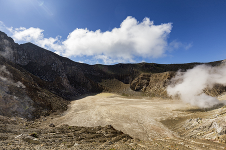 The caldera on Mount Egon with a small acidic lake and sulphuric gasses coming from within the volcano. Stock Photo
