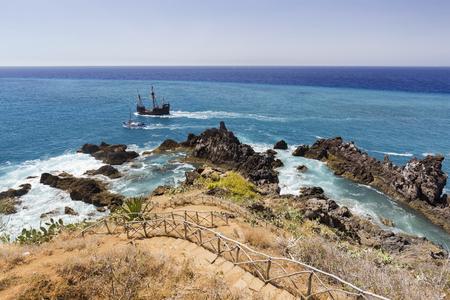 Two boats float past rocky coastline near Sao Martinho in Madeira, Portugal.