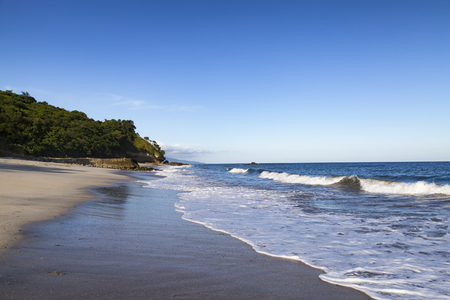 Afternoon light and small waves on an empty beach in Paga, East Nusa Tenggara, Indonesia. Stock Photo