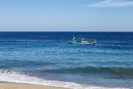A fishing boat sails down beach in Paga, Indonesia.