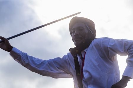 BAJAWA, INDONESIA - MAY 19: An unidentified man dances with a pole at a boxing match near  Bajawa in East Nusa Tenggara, Indonesia on May 19, 2017. Editorial