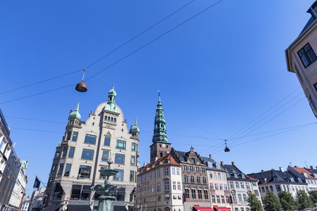 The Stork Fountain with beautiful Danish buildings and a Church Spire. Archivio Fotografico - 123571780