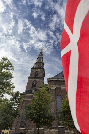 Portrait view of a Danish flag and the Church of our Savior in Copenhagen, Denmark. Archivio Fotografico - 123633815