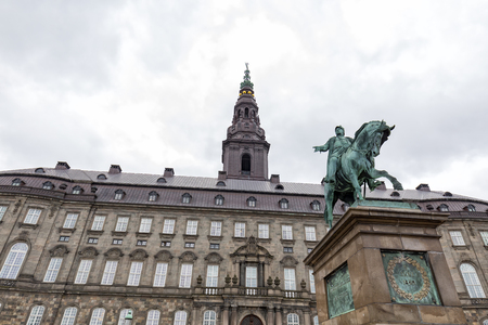Storm clouds over the Christiansborg Palace and Frederik VII statue. Archivio Fotografico - 123571799