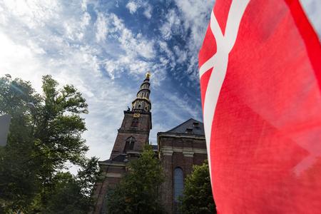 The Church of our Savior with the Danish Flag in Copenhagen, Denmark. Archivio Fotografico - 123633938
