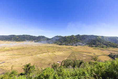 Smoke rising from the Spider Rice fields during harvest season in Flores, Indonesia.